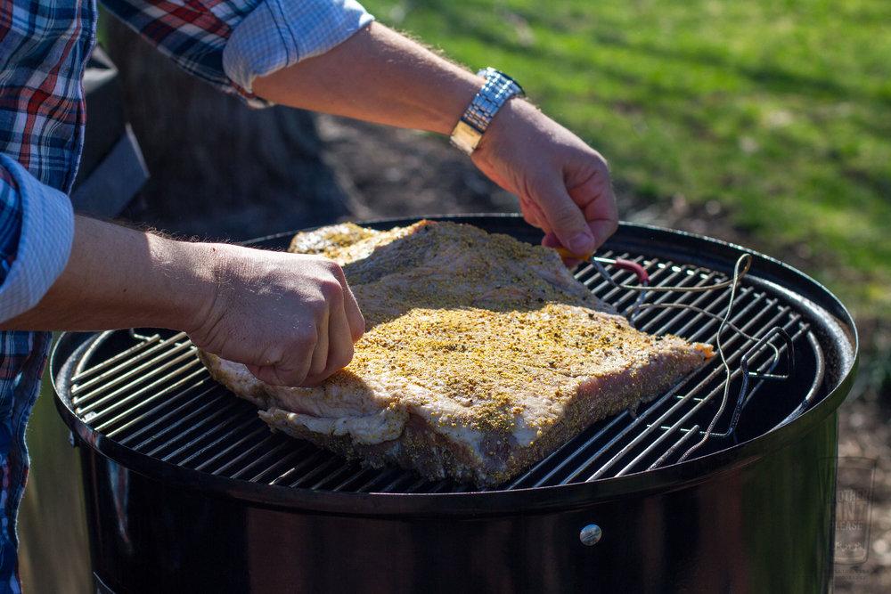 placing pastrami on weber smokey mountain cooker.jpg