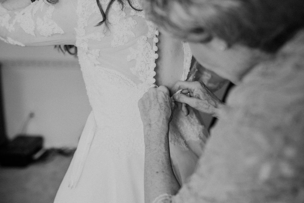 mom buttoning up bride's dress