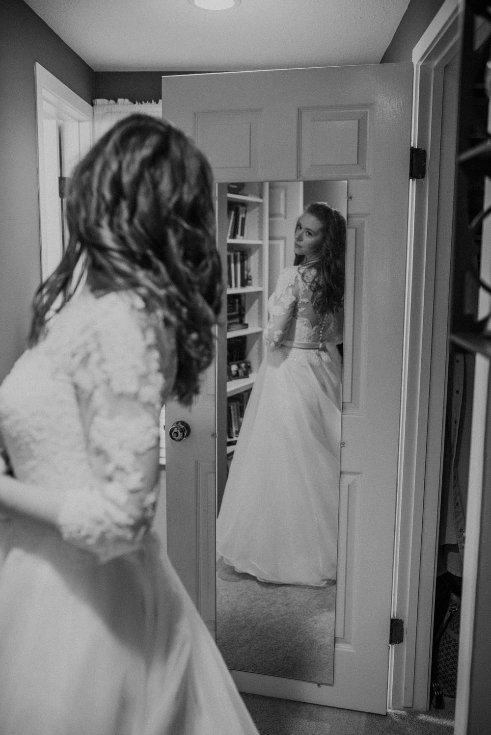 black and white bride getting ready and looking at dress in the mirror