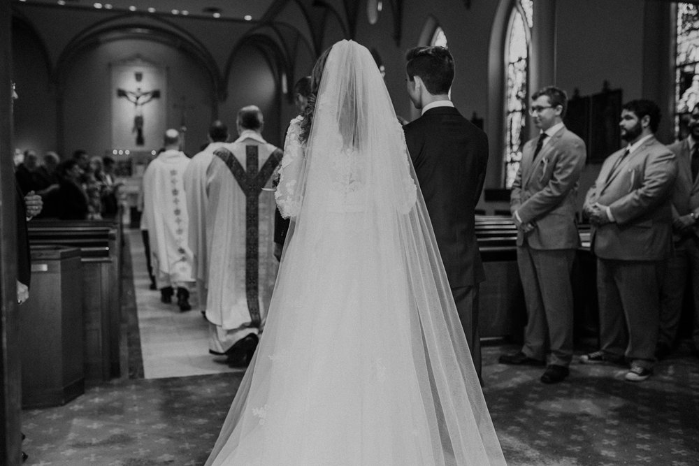 catholic wedding procession of bride and groom into church