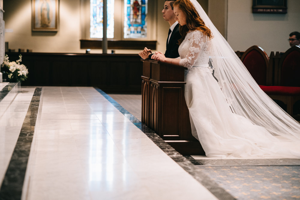 bride and groom kneel before altar at old saint mary catholic church