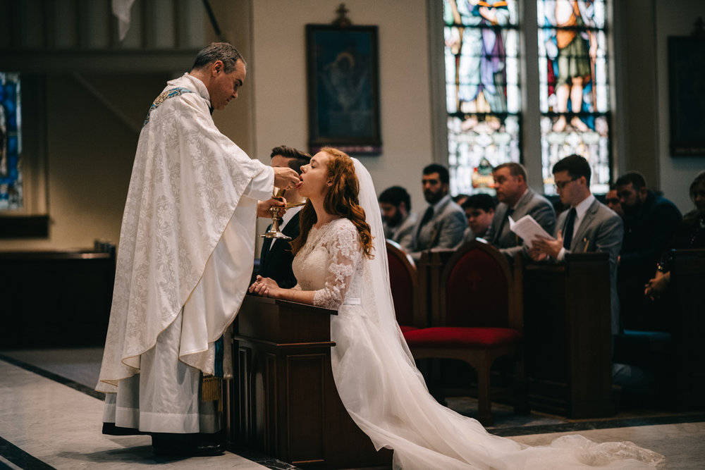 bride receives eucharist during wedding