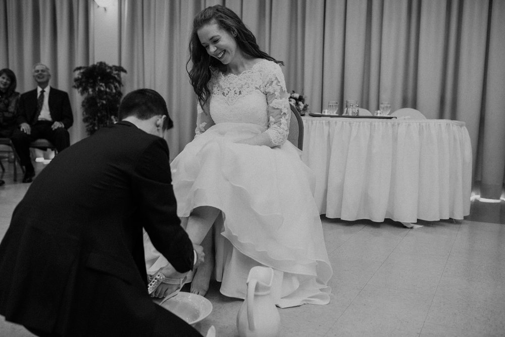 catholic wedding groom washes bride's feet