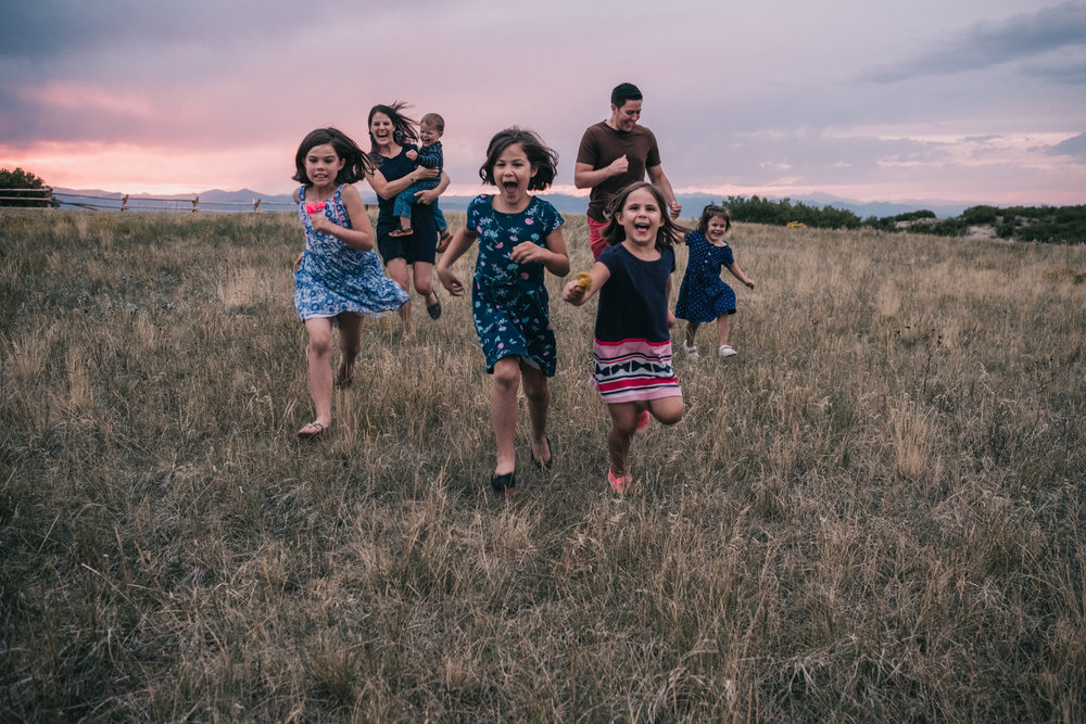 Colorado family portrait lifestyle session family running across a field