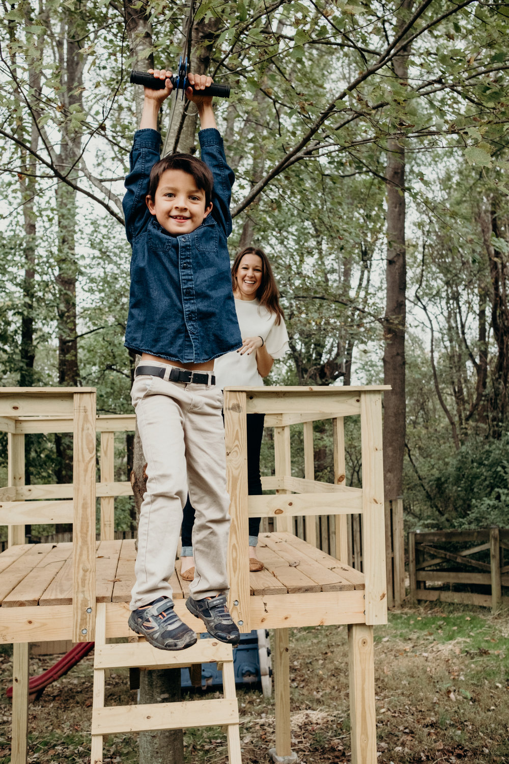 boy ziplines in backyard during family photo session