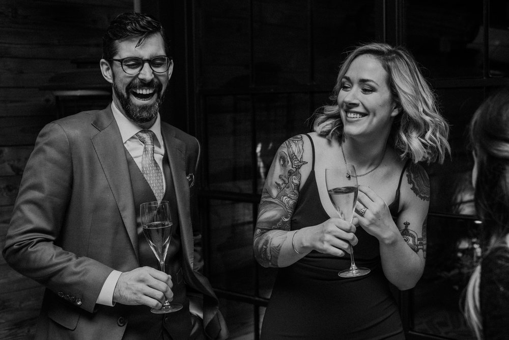 bride and groom laughing during toasts at their wedding