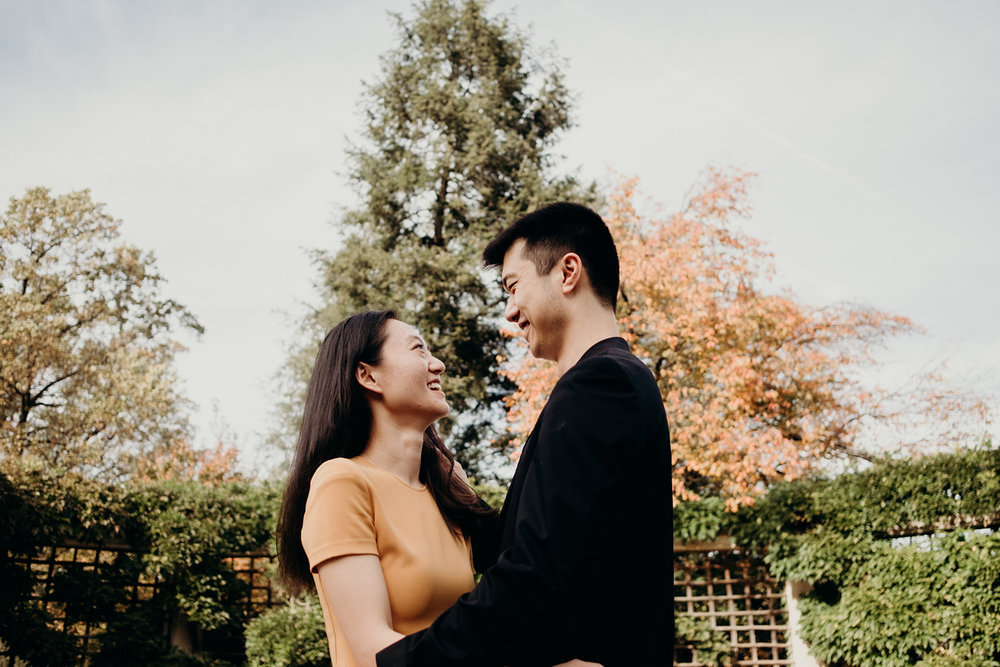 An engaged couple smiles while surrounded by fall foliage.