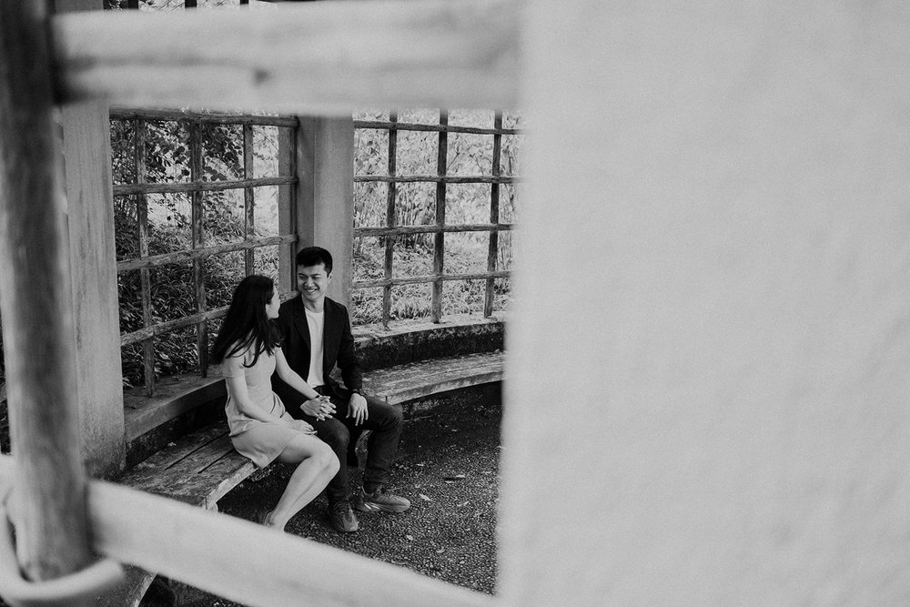 An engaged couple smiles at one another in a gazebo at Dumbarton Oaks.