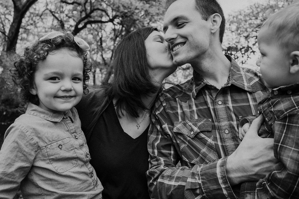 A mother kisses her husbands cheek while her children smile.