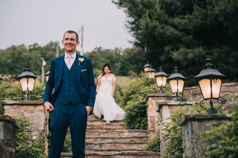 groom waits as bride walks down steps to meet him during first look at Bluemont Vineyard