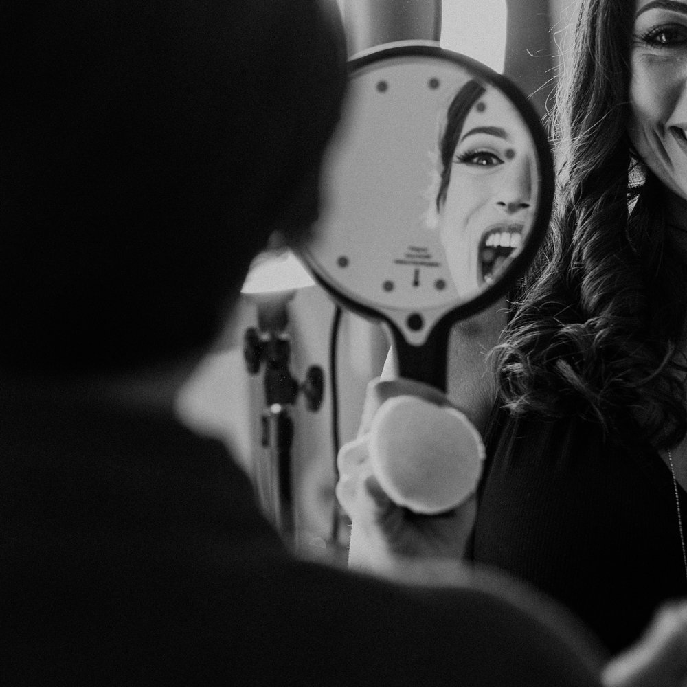 bride with huge smile in mirror as she sees her makeup before wedding