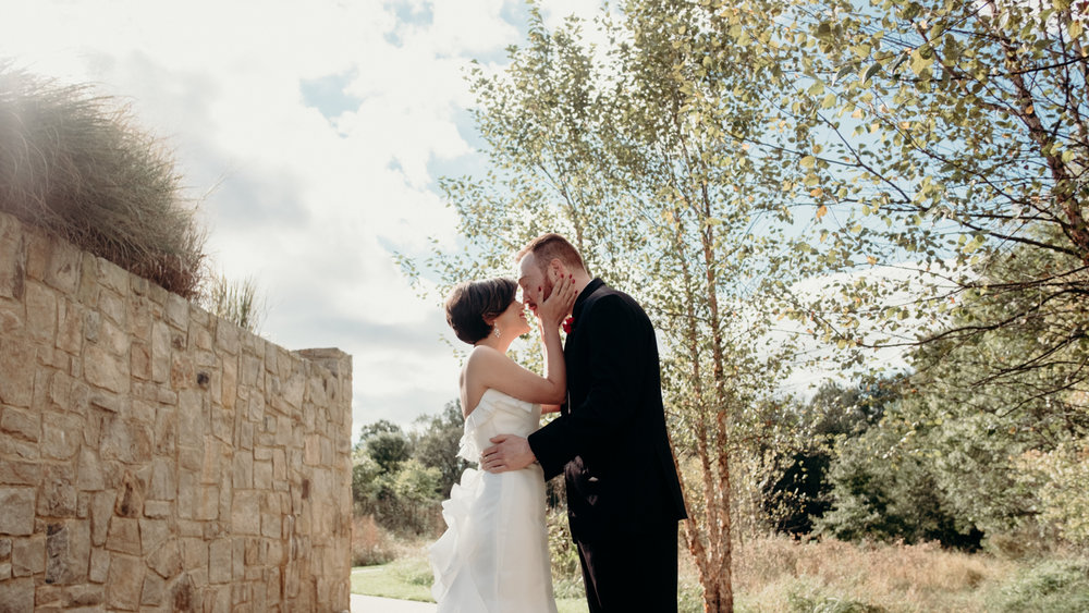 bride and groom kiss during first look at middleburg wedding