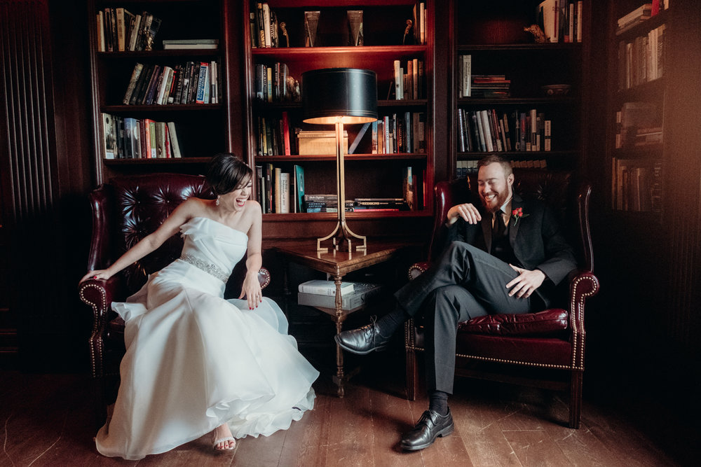 bride and groom sit and laugh before their wedding in the library at Salamander Resort and Spa