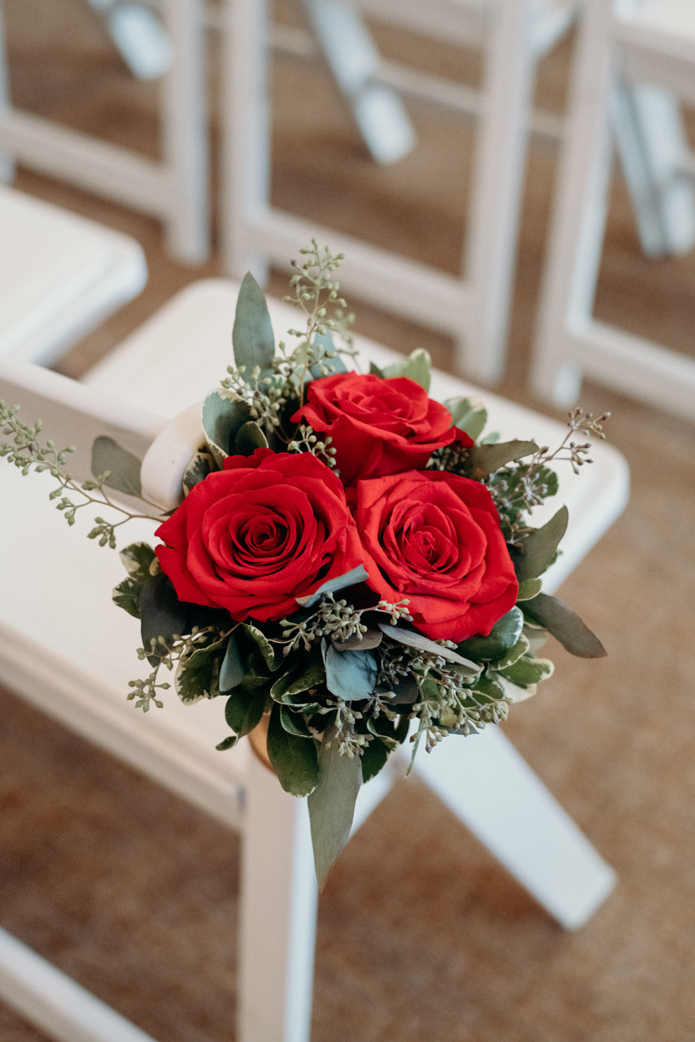 floral arrangement on ceremony chairs at middleburg wedding