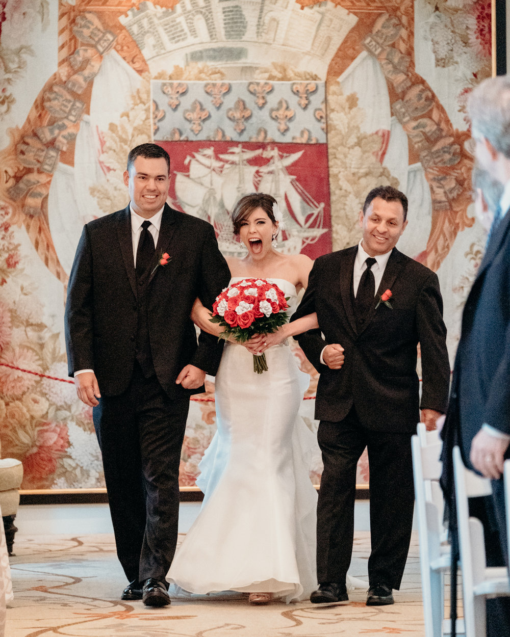 Bride escorted by uncles down the aisle laughs in joy at her wedding