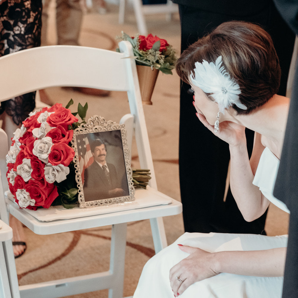bride stops to kiss the picture of her late father before the start of wedding ceremony
