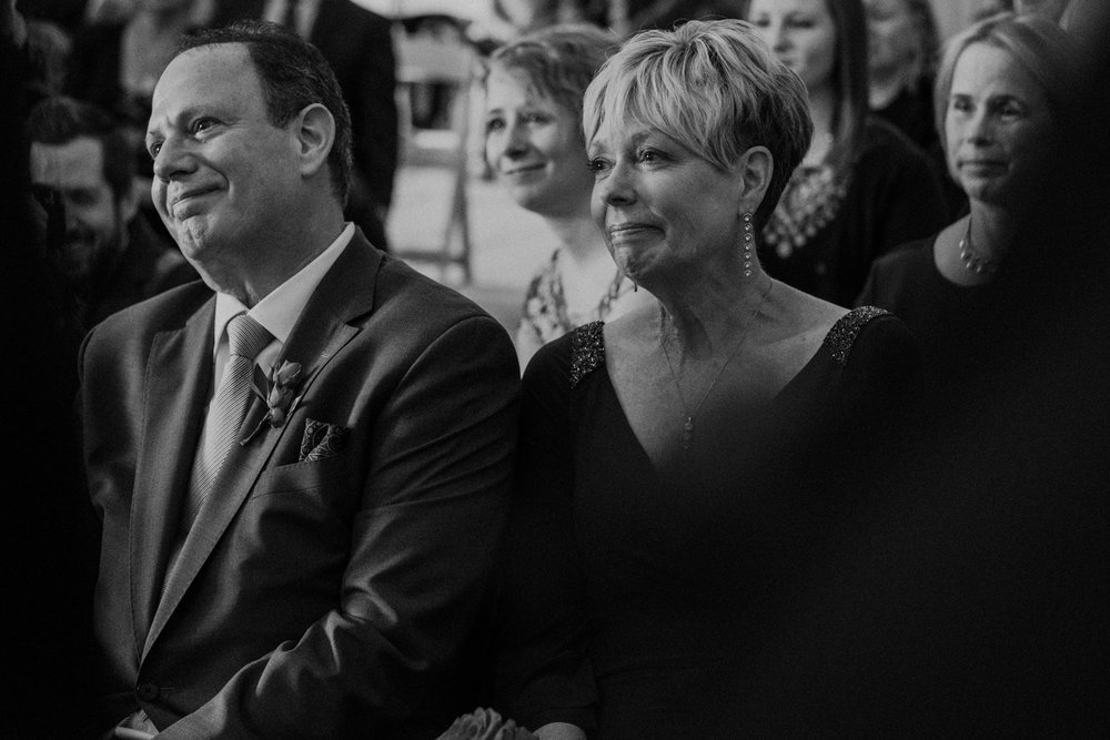 Groom's parents listen on with tears in eyes as they're son reads his vows