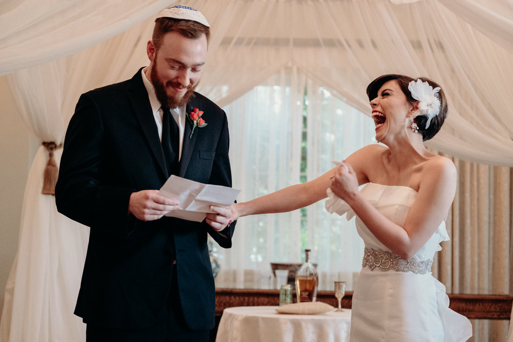 Bride laughs during groom's personal vows