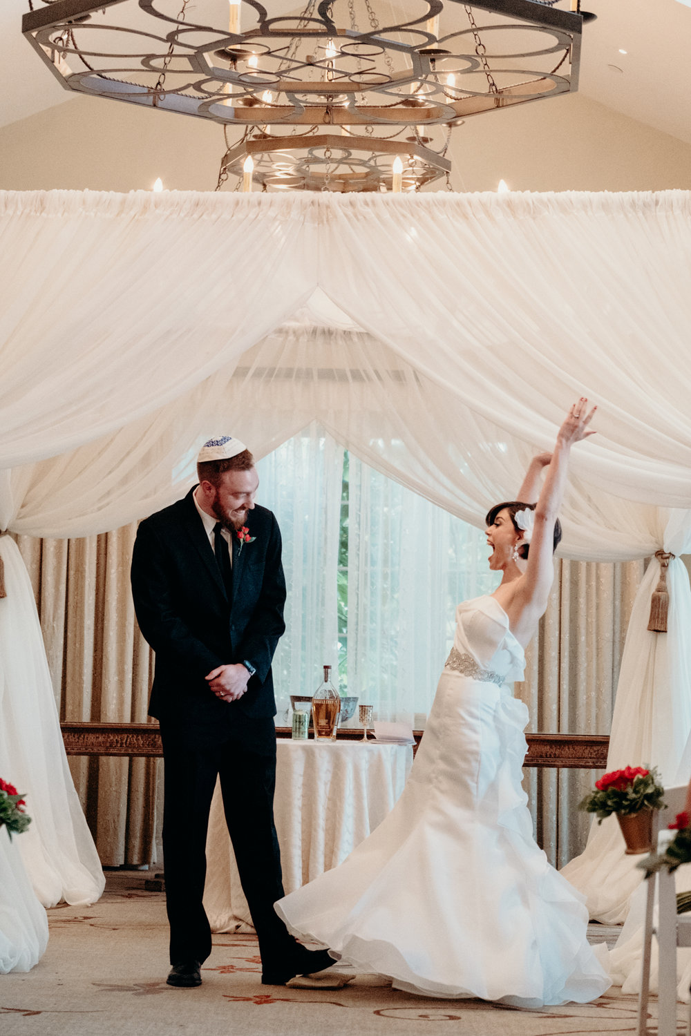bride throws up her hands in excitement as they are pronounced husband and wife after breaking of the glass