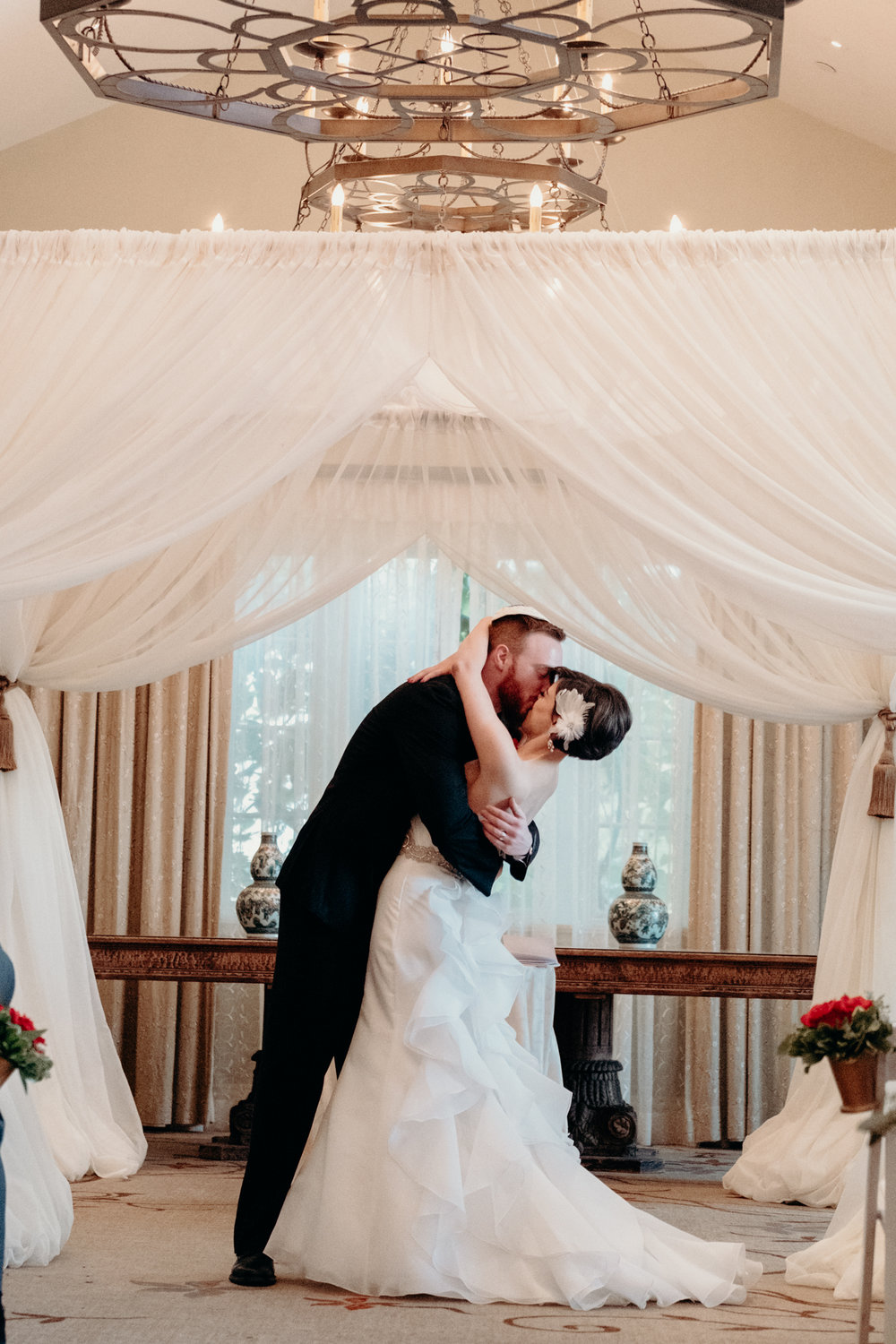 bride and groom kiss after breaking the glass