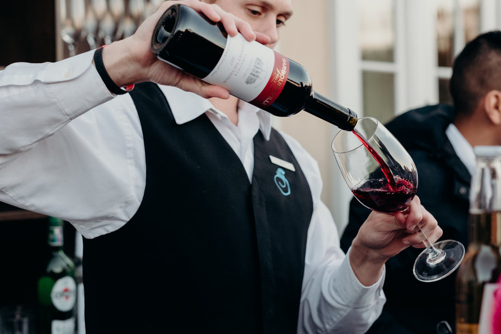 bartender pours wine for guests during virginia wedding cocktail hour