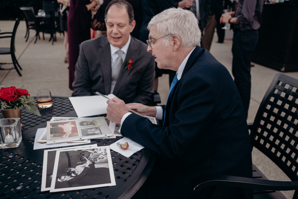 father of groom and guests look at old wedding photos during cocktail hour
