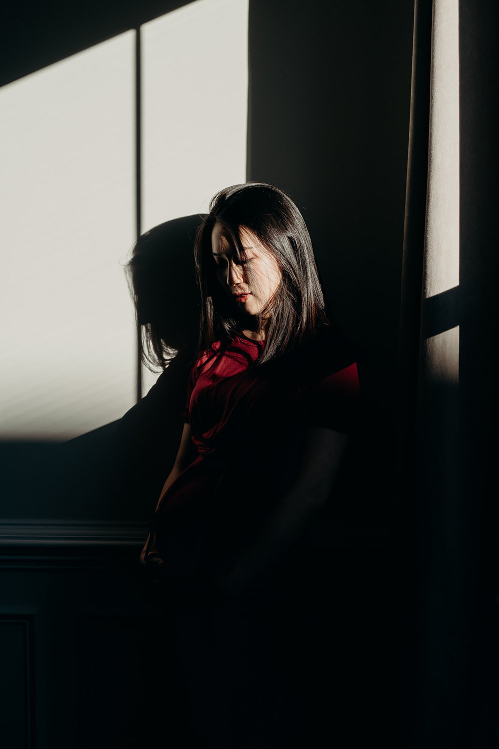 An expectant mother looks down at her baby bump hiding in the shadows while her face is illuminated by the light.