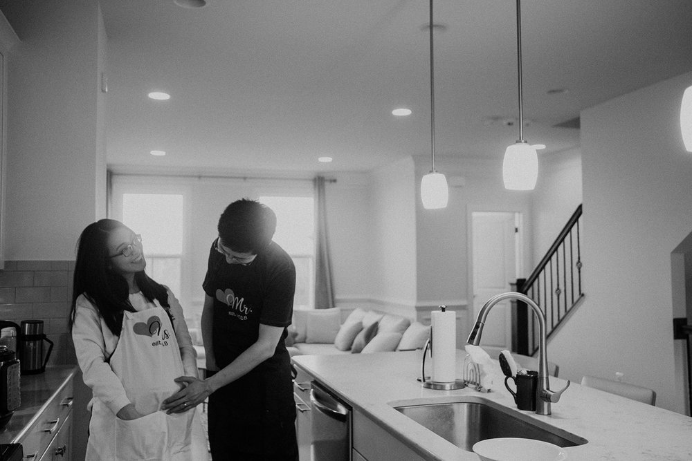 A proud father gently touches the belly of his pregnant wife in the kitchen of their new home.