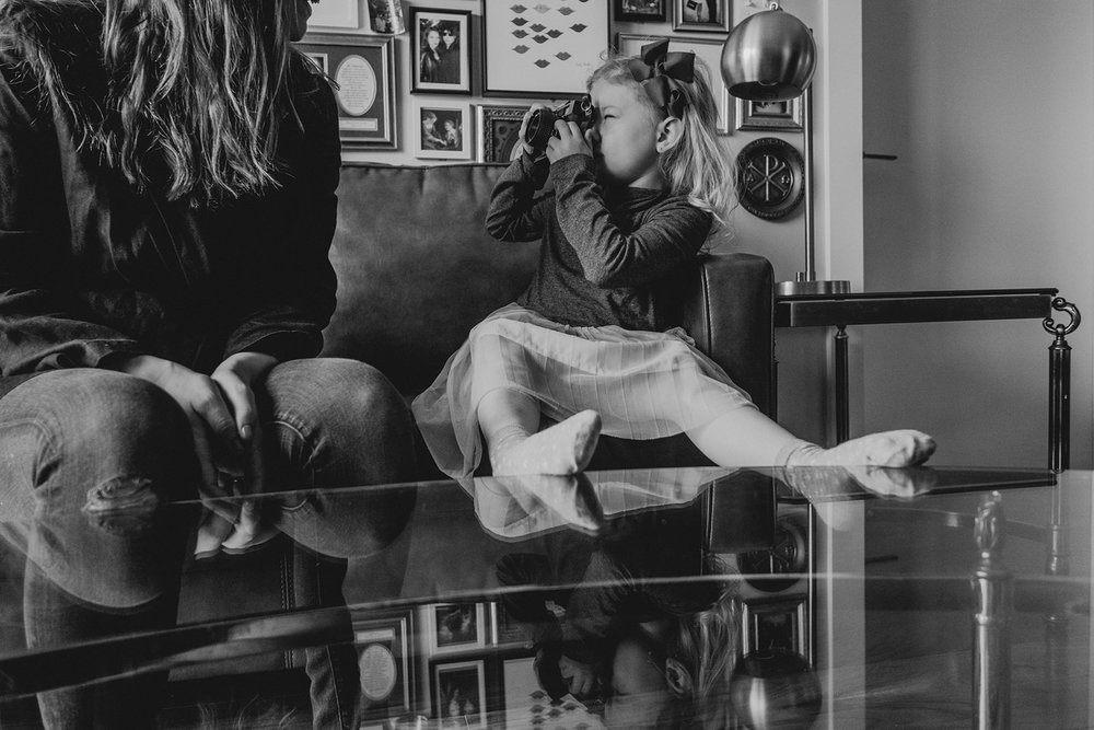 A little girl takes a picture of her mother while seated on a couch in their apartment in Washington, DC.