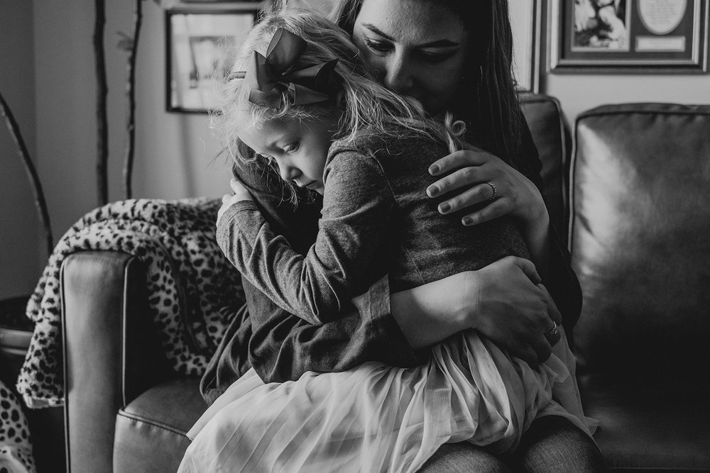 A mother embraces her daughter while sitting on a couch in their apartment in Washington, DC.