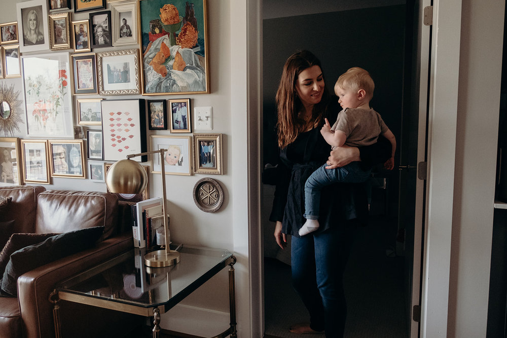 A mother holds her little boy before putting him down for a nap in their apartment in Washington, DC.