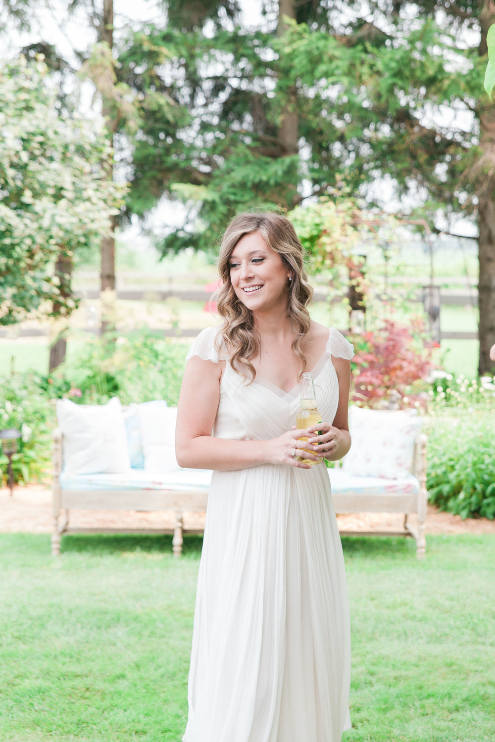 Bride at cocktail hour at farm wedding
