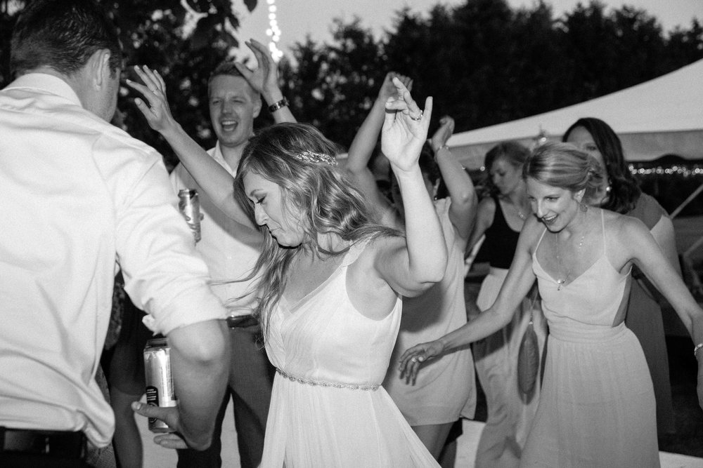 Bride dancing with guests under twinkle lights