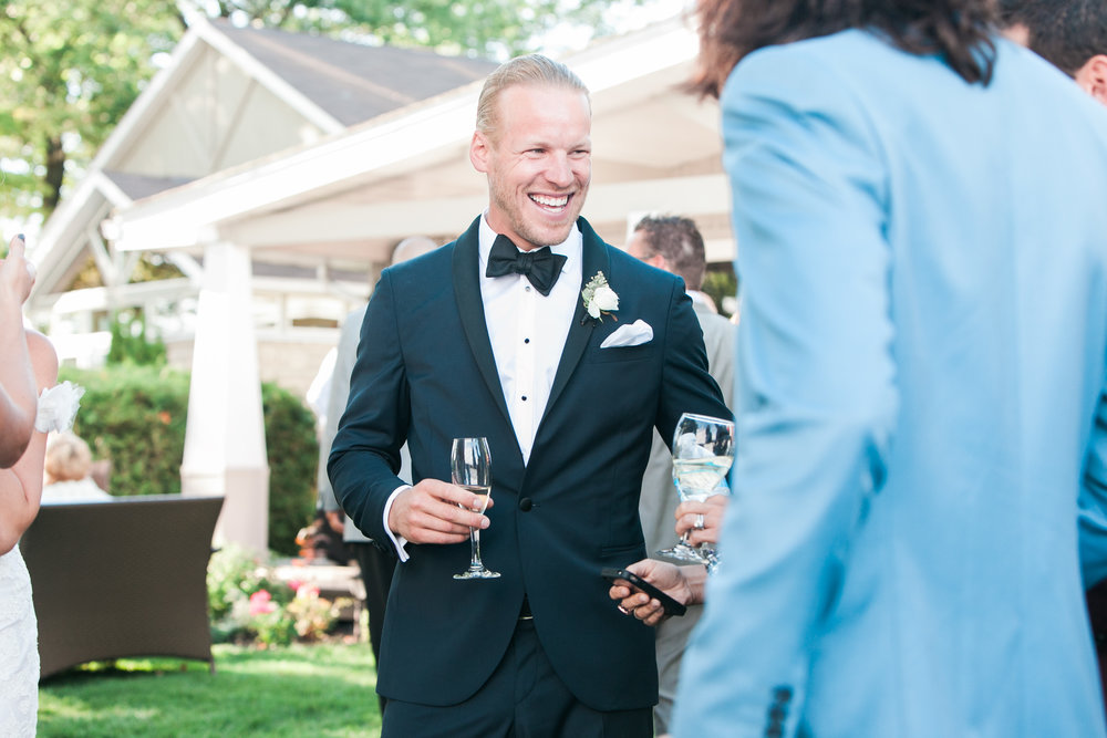 Groom laughing at cocktail hour