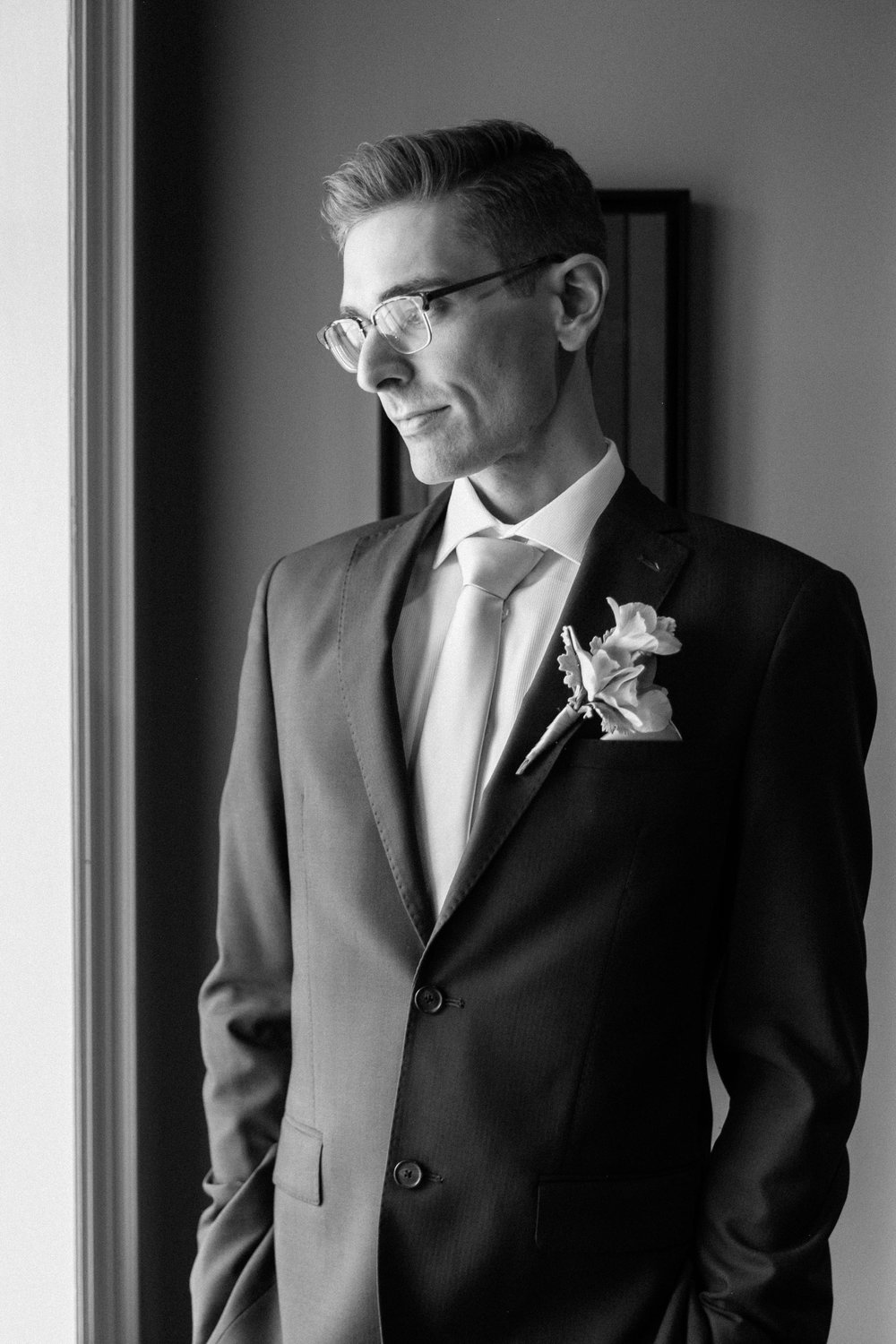 Black and white portrait of groom with glasses