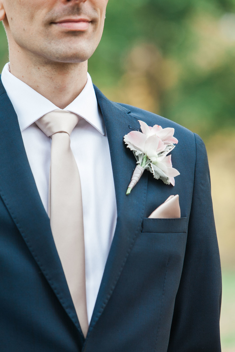 Groom wearing navy suit and blush tie
