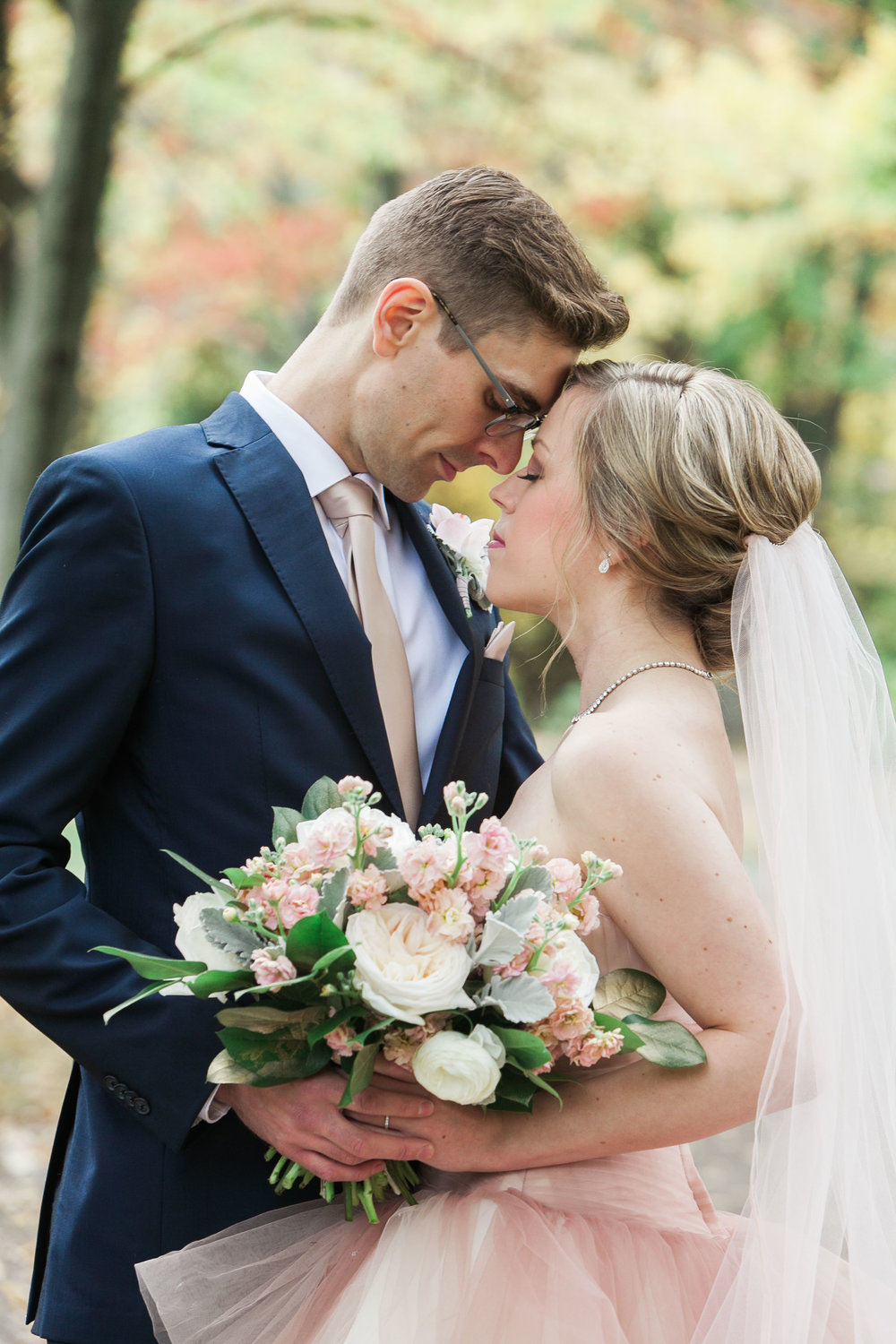 Bride in blush and groom in navy