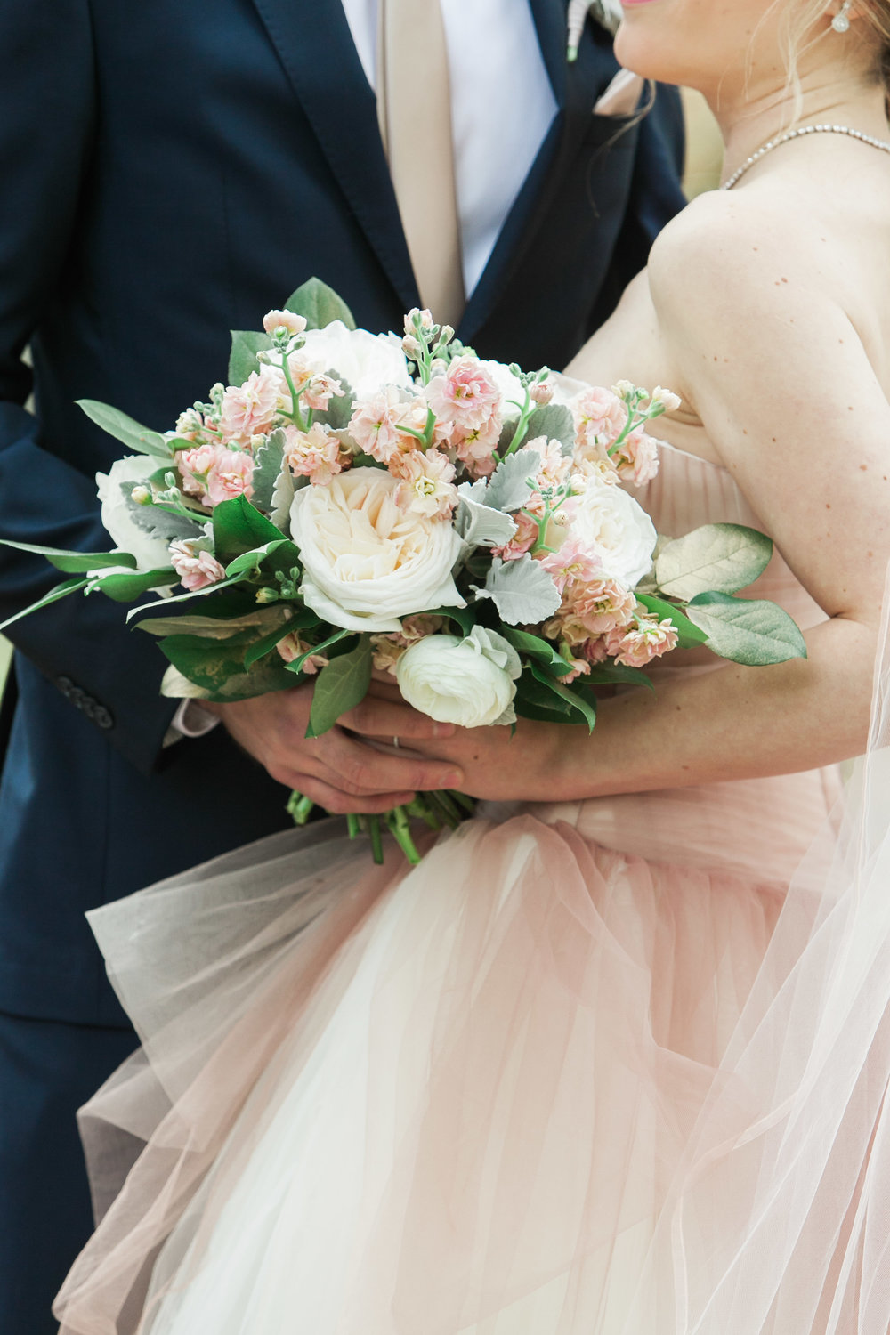 Closeup of bride holding blush boquet