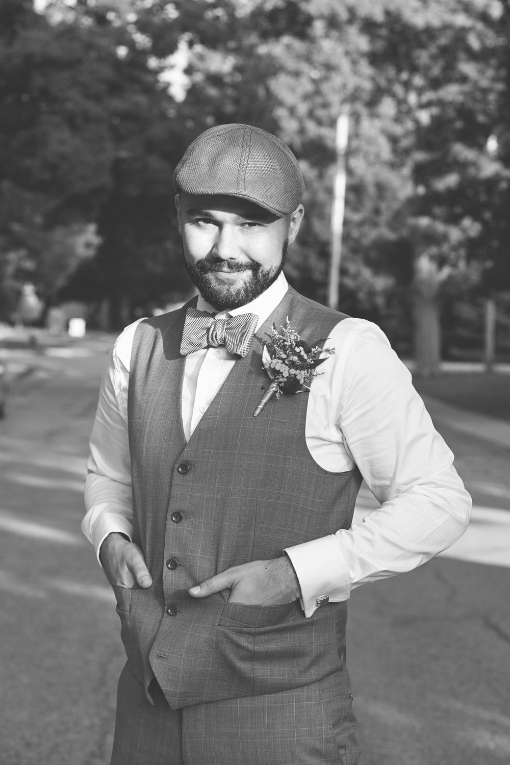 Stylish groom in grey suit and hat