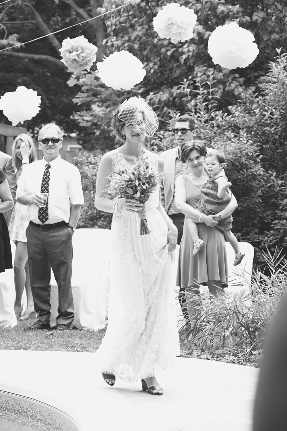 Bride walking down aisle at backyard wedding
