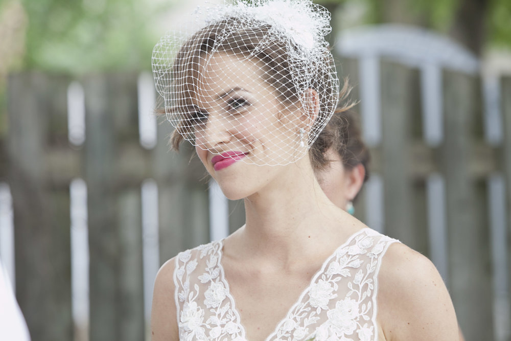 Bride wearing bird cage veil and bright pink lips