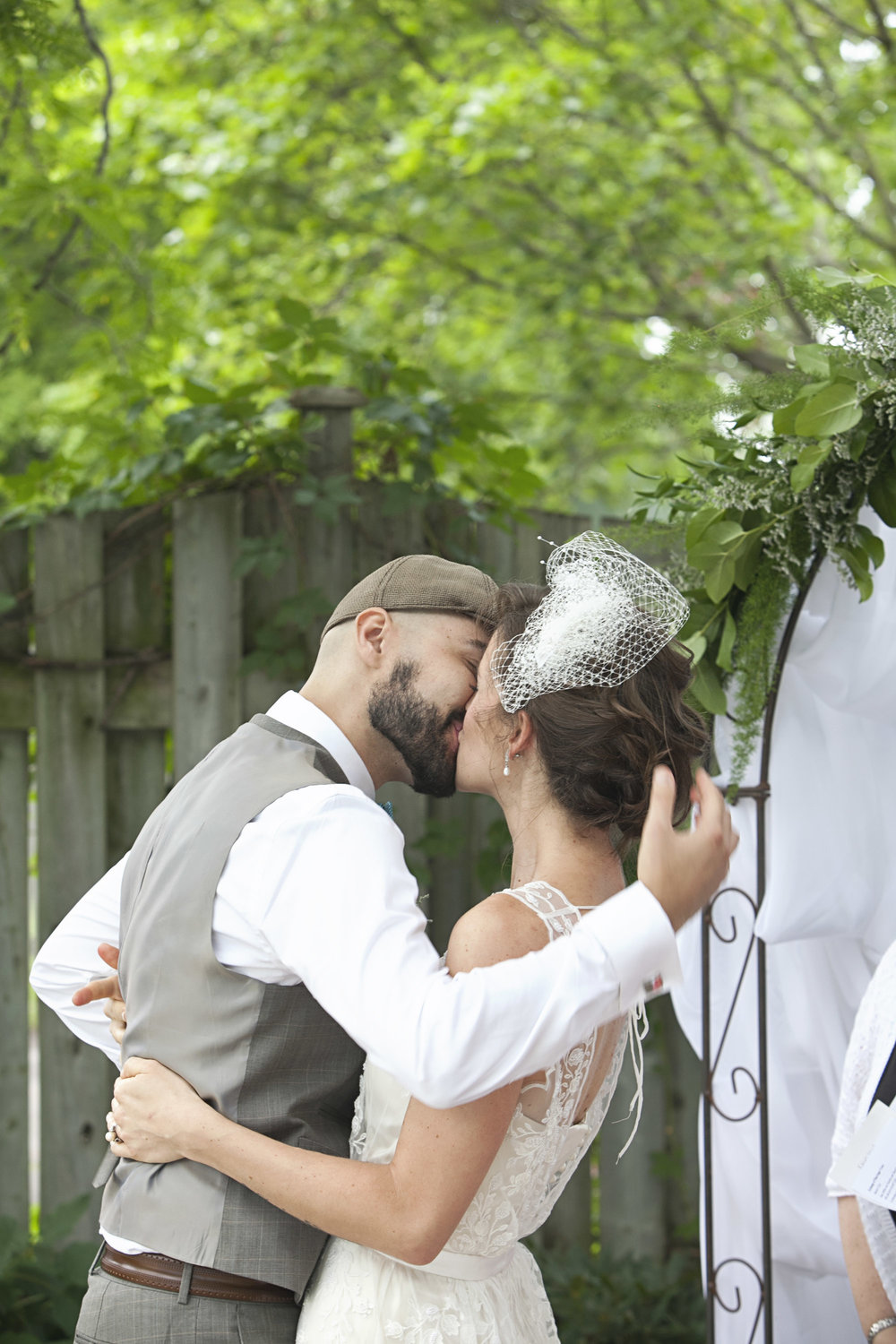 Bride and groom's first kiss at backyard wedding