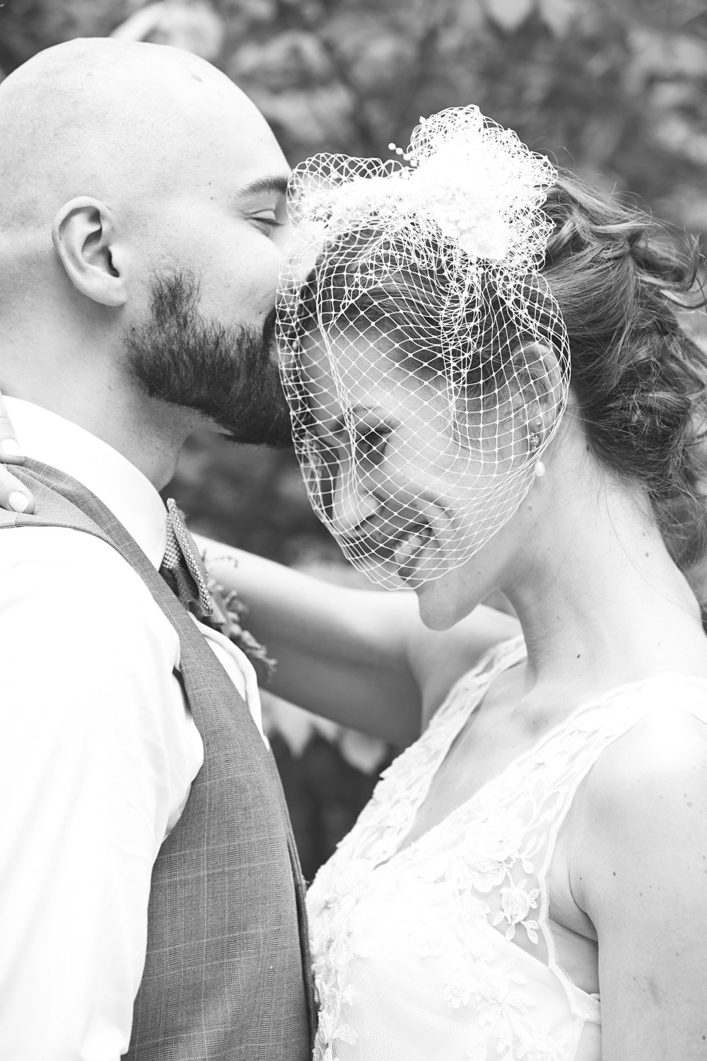 Groom kissing bride on forehead