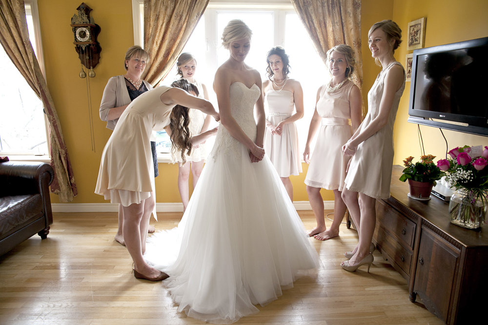 Bridesmaids helping bride put on wedding dress