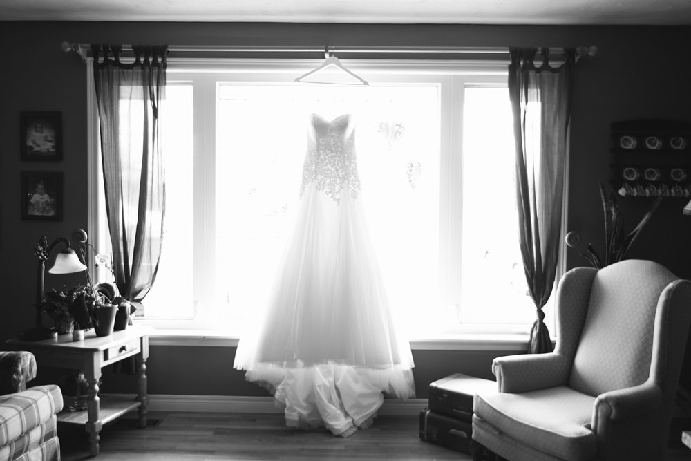 Lace and tulle wedding dress hanging from window