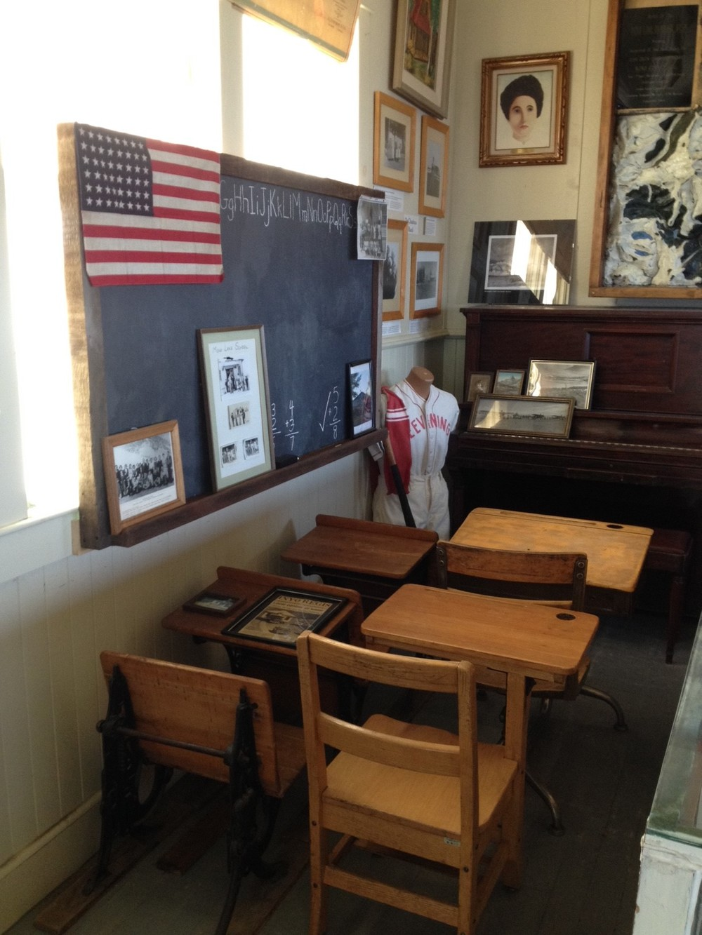 school desks by blackboard and baseball uniform on mannikin.JPG