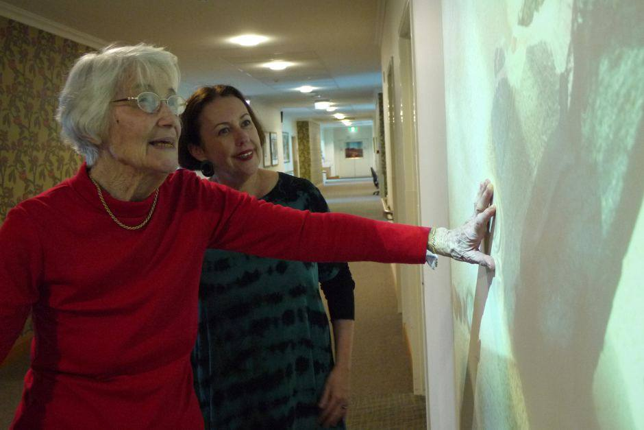 Dementia design specialist Debbie de Fiddes (right) chats with Marjorie Hartley at the interactive wall.  Photo Credit: ABC News / Rebecca Turner
