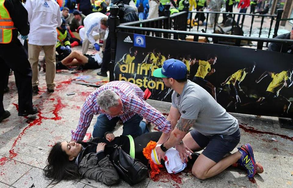 A Boston Marathon victim is being helped by bystanders who are applying pressure. Photo: Boston Globe