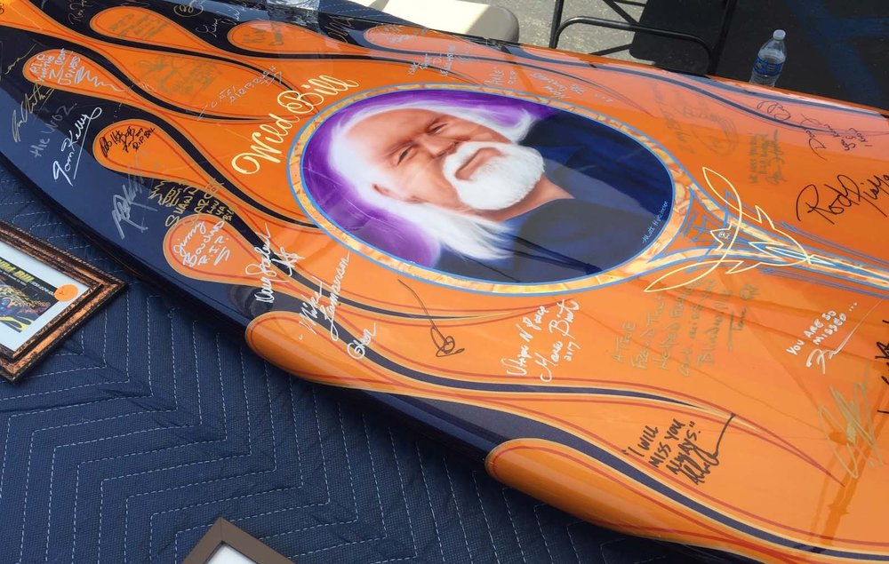 A restored surf board crafted by the late Wild Bill, sits on the display table at the Riverside Nationals Car Show. The surf board was retouched and painted by fellow pinstriper and painter, Herb Weber and rendering created by artist, Matt Hutchinson, to commemorate Wild Bill. The surf board has been taken to several car shows this Spring and signed by friends, pinstripers and family.