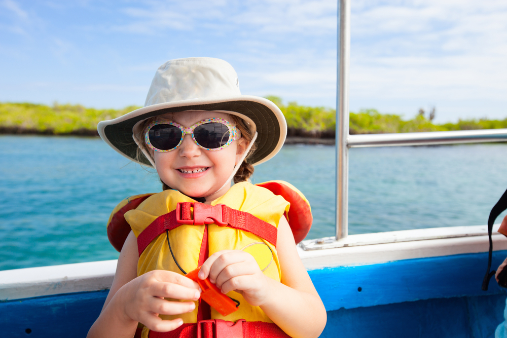Little girl enjoying boating in her sunglasses and life jacket
